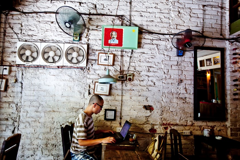 A customer uses a computer at a cafe in Hanoi, Vietnam. Photo credit: Bloomberg