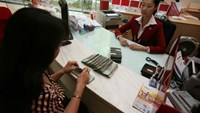 A HDBank teller watches as a customer counts packs of dong notes in Ho Chi Minh City. Photo: Dao Ngoc Thach