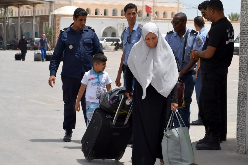 A Libyan woman fleeing the violence in her country enters Tunisia through the southern border crossing at Ras Jedir on July 30, 2014. Photo credit: AFP
