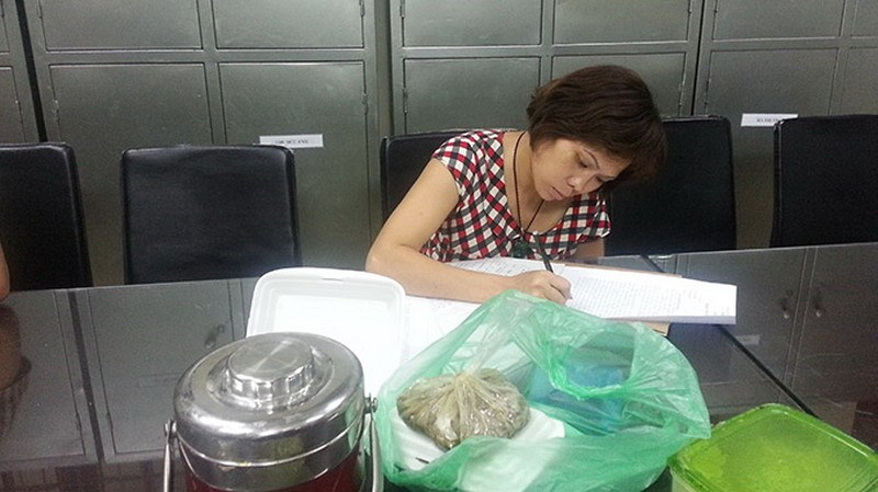 Nguyen Thi Thanh Trang, who helped manage an orphange at Bo De pagoda in Hanoi, writes a report at a Hanoi police station as she was suspected for selling a child at the pagoda. Photo credit: Tuoi Tre