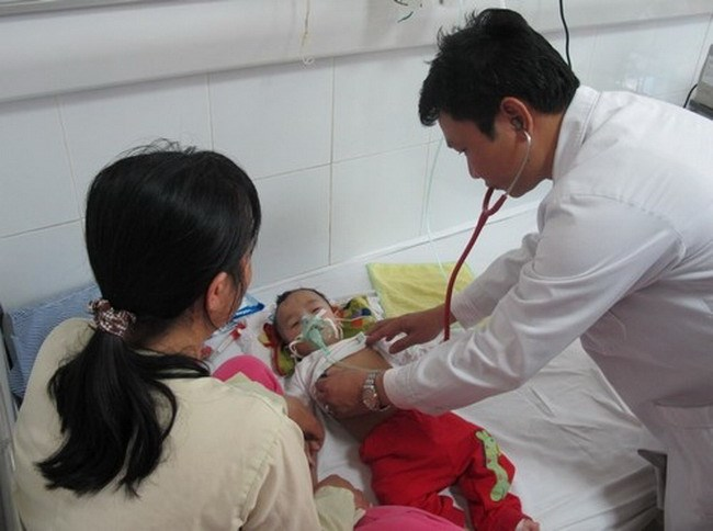 A doctor examines a baby at a hospital in Hanoi. Photo credit:VnExpress