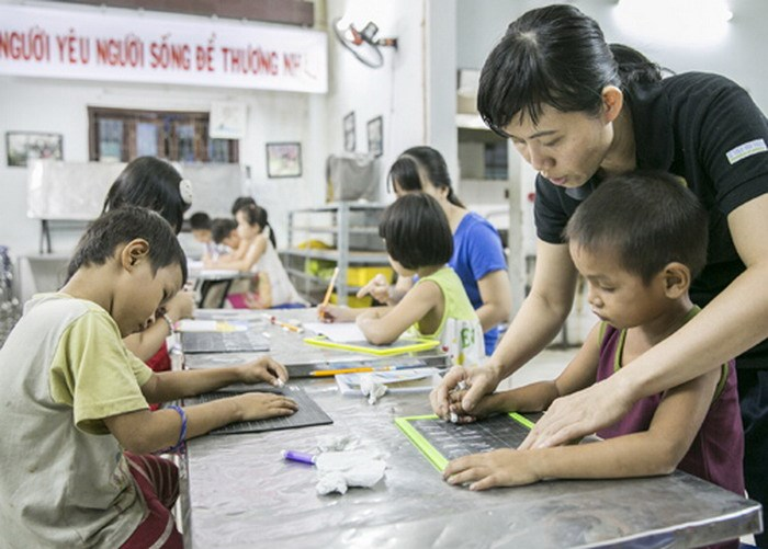 Do Thi Kim Dung, a voluntary teacher at Nu Cuoi charity class in Ho Chi Minh City, helps a 5-year-old boy writes letters on his board. Photo: Nguyen Tap