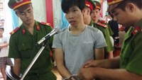 Nguyen Hau Em, 22, is escorted by the police to a trial in Ba Ria-Vung Tau Province August 7, 2014, where he was sentenced to one year in jail for stealing six dogs. Photo: Nguyen Long