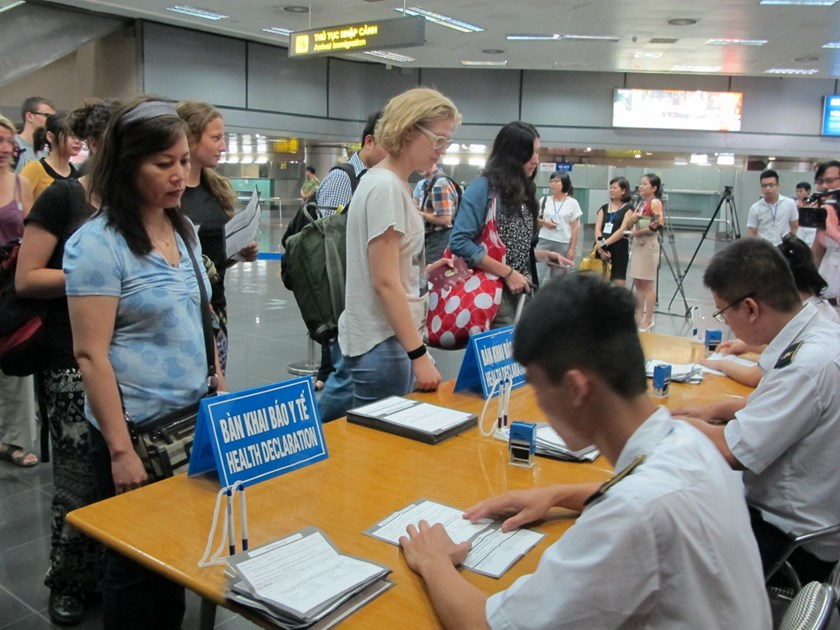 Arrivals at Noi Bai International Airport in Hanoi wait as officials check their health declaration amid Ebola scare. Photo: Duong Ngoc