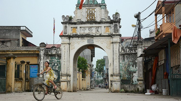 A girl rides past the gate of Khe Tang village on the outskirts of Hanoi, which banned the burning of votive paper offerings in 2012. Photo credit: Tuoi Tre