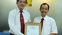 Vinasun taxi driver Hoang Thanh Hung (R) is awarded by his boss August 11, 2014 for voluntarily returning a bag containing US$5,000 and other assets to customers. Photo credit: VnExpress