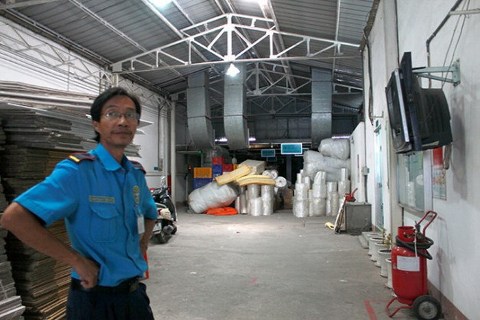 A photo taken on August 12, 2014 shows a guard at Austria-owned Bach Hop garment company in Ho Chi Minh City, which has been emptied as the boss and representatives fled. Photo credit: Tuoi Tre