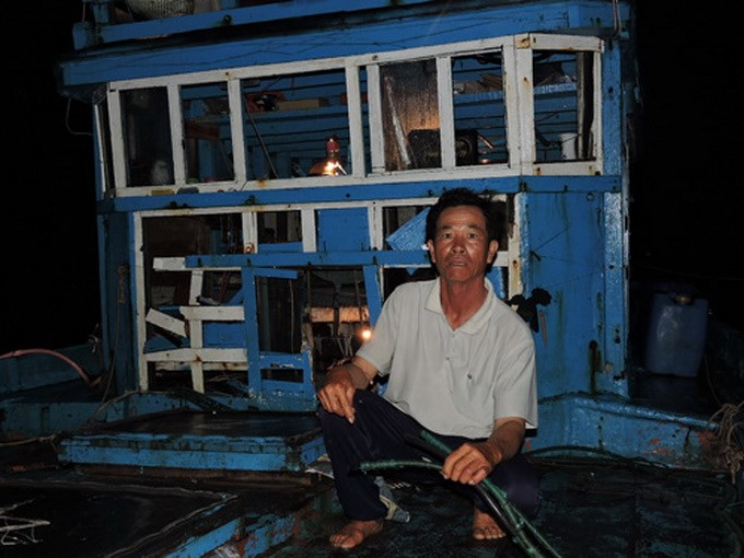 A Vietnamese fisherman sits on his boat which was damaged after a Chinese attack on August 14, 2014. Photo: Hien Cu