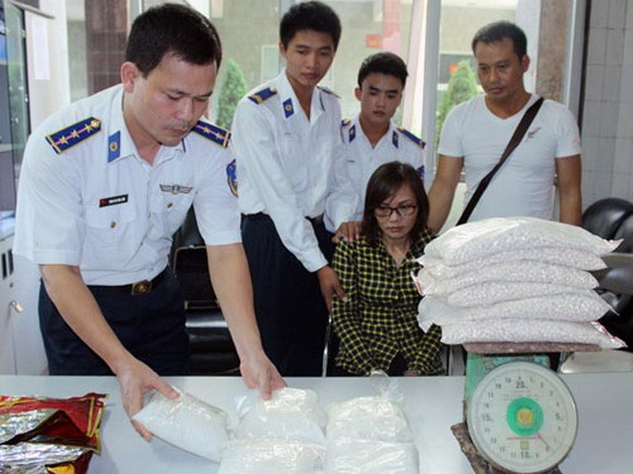 Le Thi Thuc, 40, being held at a Hai Phong police station as the officers weigh 13 kilograms of meth and ecstasy pills. She and her two male accomplices were caught with the drugs on August 17, 2014. Photo: Lam Giang
