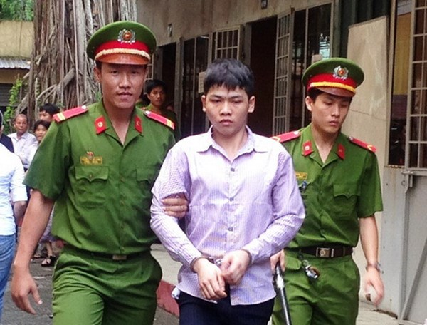 Nguyen Van Tuan, 18, being escorted out of a courtroom in Ho Chi Minh City on August 20, 2014. The boy received 18 years in jail for stabbing an innocent man to death. Photo: Huong Giang
