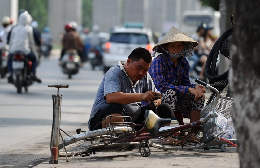 A roadside bike repairman fixes an inner tube for a customer on a street in Hanoi. Photo: Hoang Dinh Nam/AFP
