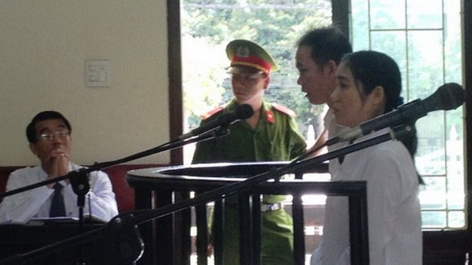 Ho Thi Thu Huong, a former BIDV bank teller, and her brother-in-law at their appeals trial in Binh Dinh Province on August 28, 2014. Huong was convicted of stealing nearly $1.5 million from her employer. Photo credit: Tuoi Tre