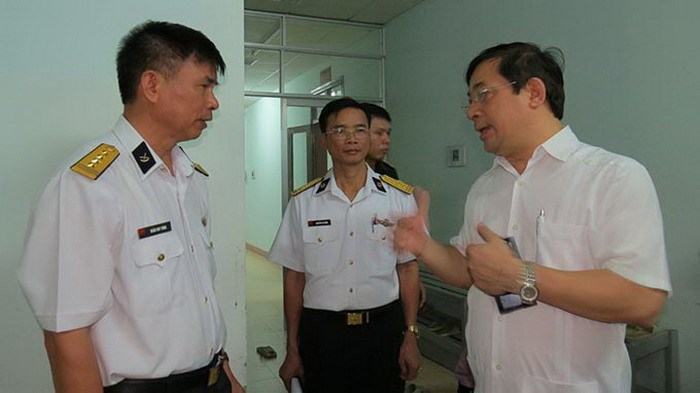Luong Ngoc Khue (R), head of the Examination and Treatment Department at the health ministry, visits a military hospital in Khanh Hoa Province where surgeries performed by a Hanoi charity on August 23, 2014 claimed three infants' lives. Photo credit: Tuoi