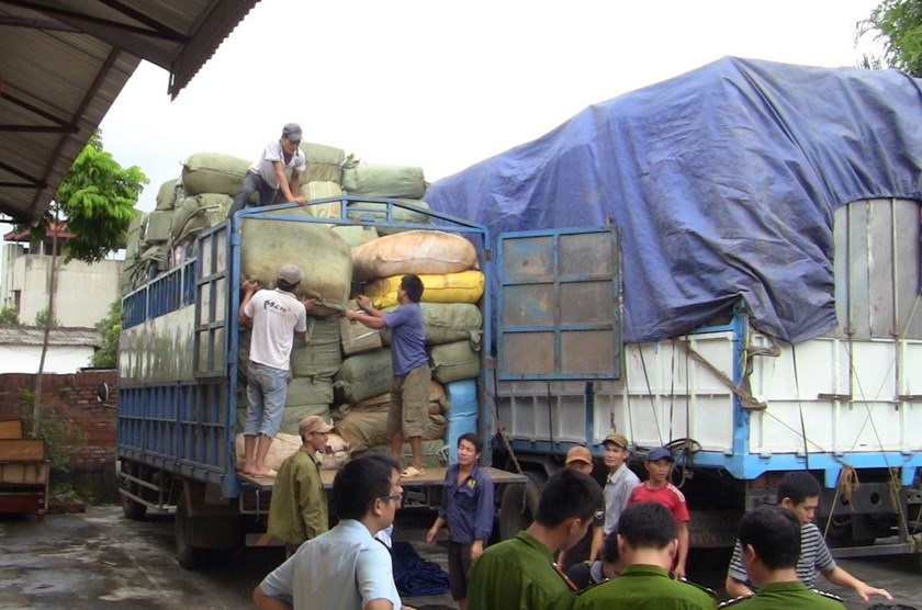 Workers unload sacks of illegal Chinese cargo after seizing eight trucks on the night of August 31, 2014. Photo: Quang Hung