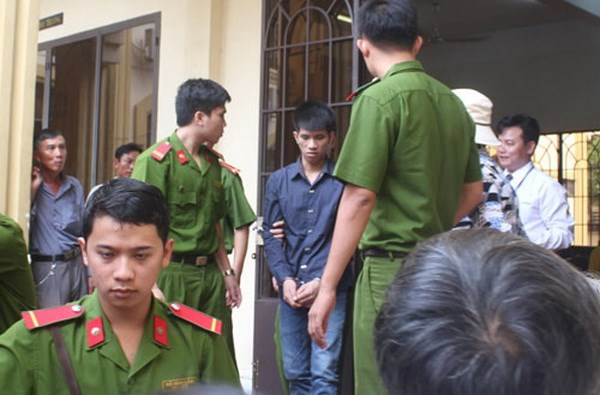 Do Van Cuong (C) being escorted out of a court house in Dong Nai Province on September 12, 2014. Photo: Le Lam