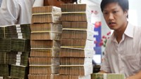 Employees count money at a branch of Vietnam's Bank of Investment and Development (BIDV) in Hanoi. Photo: Kham/Reuters