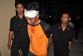 Police officers in Binh Thuan Province escort the alleged ringleader of a gang of armed robbers six armed men arrested on the evening of September 18, 2014. An eighth member of the gang is reportedly still at large. Photo: Mai Thanh Hai
