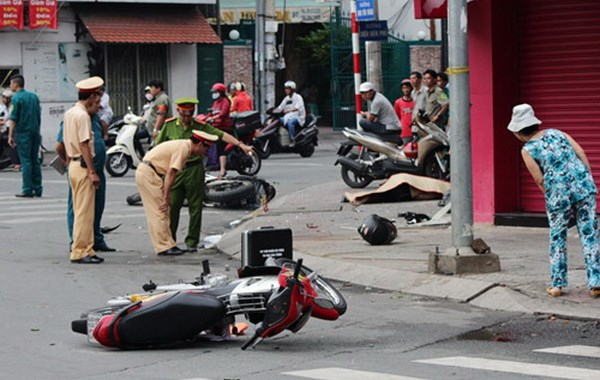 Police examine the crash site in Ho Chi Minh City where a foreigner was killed after running his motorbike into a wall on the sidewalk on September 21, 2014. Photo: Duc Tien