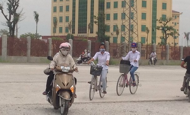 Everyone in Bong Lang village in Ha Nam Province wears a face mask on the street to protect themselves from the dust produced by an abundance of factories in their area. Photo: Hoang Long