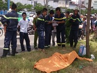 Police and rescuers surround the body of a bag snatcher who jumped into a canal in Ho Chi Minh City to escape the police on September 30, 2014 and drowned. Photo: Thanh Van