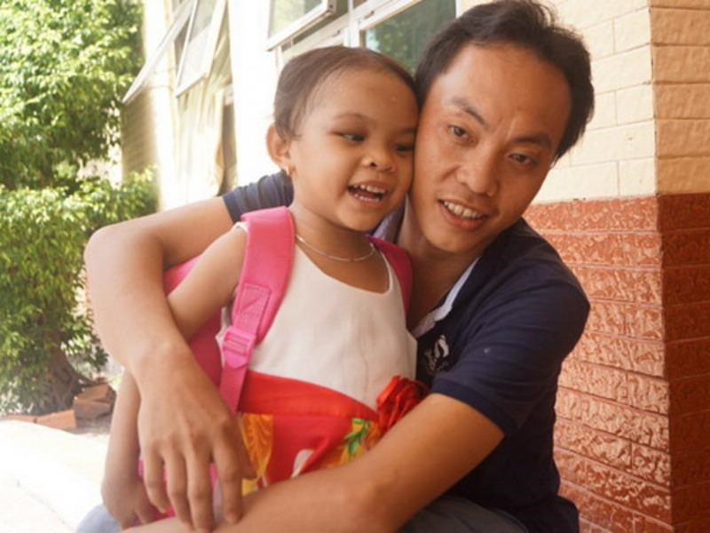 Tran Thi Kim Ngan, 3, with her estranged father Tran Van To at a hospital where doctors treated injuries inflicted by her mother and step-father. Photo: Do Truong