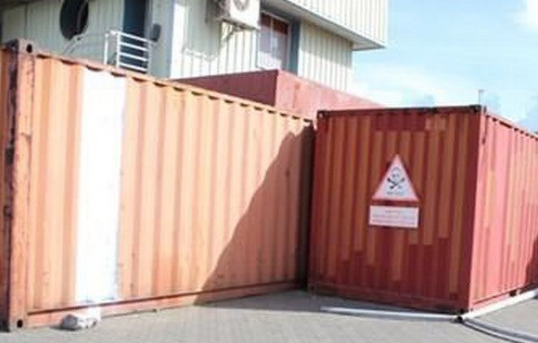 Containers loaded with 7,000 liters of contaminated oil sit outdoors at a port near Ha Long Bay. Photo credit: Vietnam News Agency
