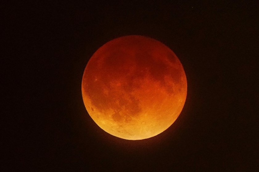 A lunar eclipse unfolds over Southern California, April 15, 2014. This blood moon is the first of four lunar eclipses in 2014 and 2015. Photo: Joe Klamar/AFP/Getty