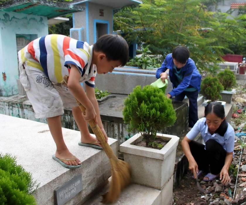 Kieu Thi Anh Lien (R) and her sons clean tombs for money at Ho Chi Minh City's Binh Hung Hoa Cemetery, where they have lived for around five years. Photo: Nhu Lich