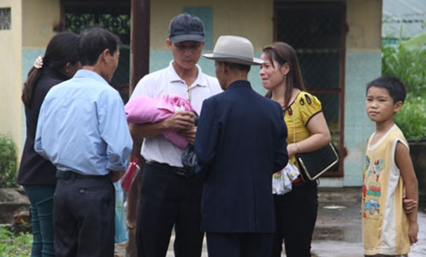 A man cradles his newborn baby among heartbroken family members after a doctor and nurse made a fatal mistake in Quang Tri Province on July 20, 2014. Photo: Nguyen Phuc