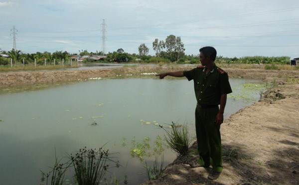 A Kien Giang police officer points to the pond where three children drowned on October 9, 2014. Photo: Xuan Lam