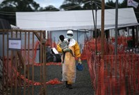 A US health worker carries a boy at an Ebola hot spot in Liberia. Photo credit: AP/Vietnam News Agency