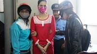 Pham Thi Nga is handcuffed around Da Nang investigators who seized a large amount of meth and ecstasy from her places on October 19, 2014. Photo: Phan Thanh/Tuoi Tre