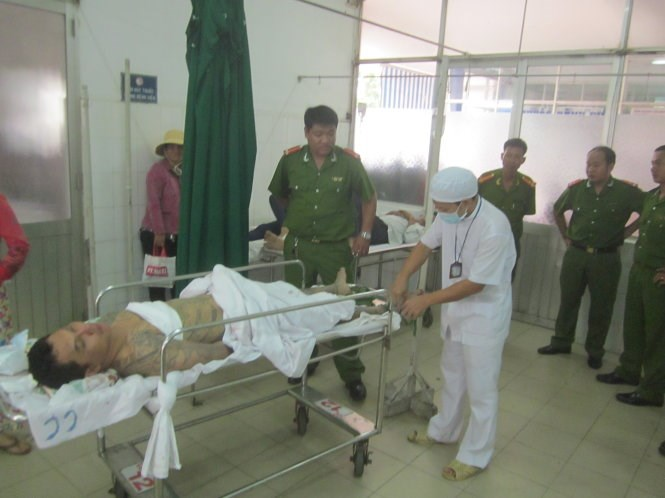 Hoang Van Thao, a drug addict who went on an axe-swinging rampage in Tien Giang Province, at a local hospital on October 23 as police keep guard. Photo: Hoai Thuong/Tuoi Tre