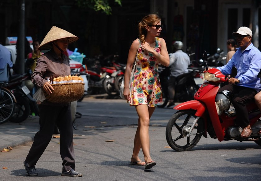 A street vendor and a foreign tourist cross a street in Hanoi's old quarter on October 9, 2014. Vendors parading the streets with colors attracts many foreigners in Vietnam, but their determination to sell also annoys the latter. Photo: Hoang Dinh Nam/AFP
