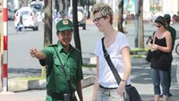 A youth volunteer gives directions outside the Nortre Dame Cathedral in Ho Chi Minh City. Photo: Trung Hieu