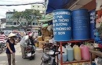 Chemical canisters and tanks sit on a sidewalk outside a market in District 5, Ho Chi Minh City. Photo credit: Tuoi Tre