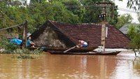 Villagers row past their flooded homes in the central province of Ha Tinh following Typhoon Nari in October 2013. Photo: AFP