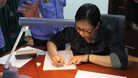 Nguyen Thi Thanh Van demonstrates how she forged a Hanoi bank teller's signature to help screate a false case against him. Photo: Hien Nguyen