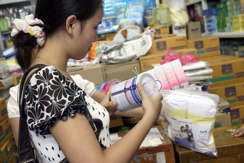 A woman checks an infant formula can at a shop in Hanoi. Photo: Ngoc Thang