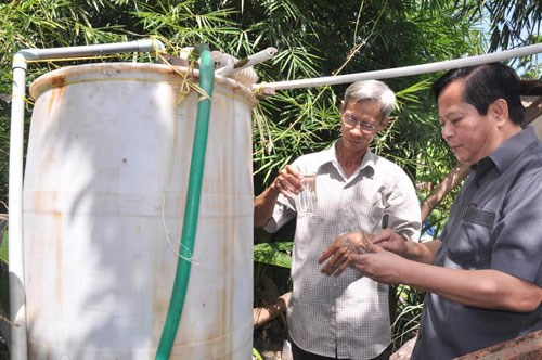 Vice Chairman Nguyen Huu Tin (R) checks the water used by a family in Hoc Mon District. Photo: Dinh Phu