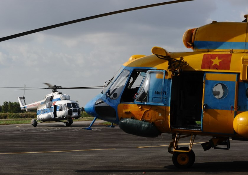 This illustrated photo shows a Vietnam Air Force helicopters (L) at Ca Mau airport in southern Vietnam as they prepare to search for the missing Malaysia Airlines flight MH370 on March 10, 2014. Photo credit: AFP