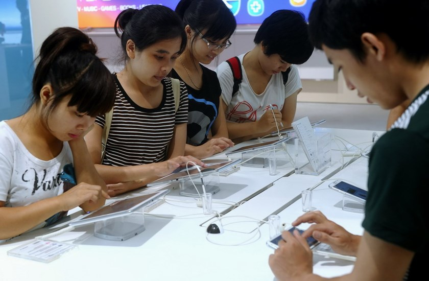 Vietnamese youths play with smart phones and tablets at a computer shop in Hanoi. Doctors say all this new technology exposes Vietnamese to information about sex at very early ages. Photo: Hoang Dinh Nam/AFP