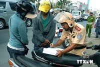 A Vietnamese traffic cop writes a ticket on the street. Photo: Bui Truong/Vietnam News Agency