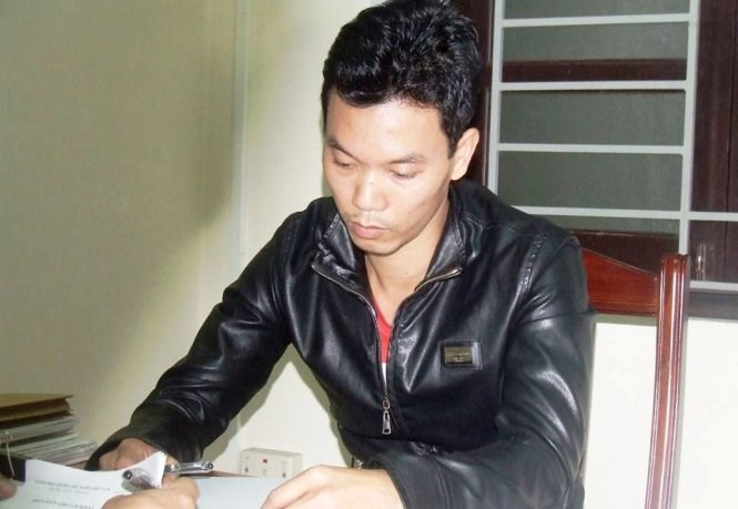 Tran Le Duc, 35, at a Nghe An police station where officers questioned him for his alleged role in a ring that helped gas station operators cheat customers out of money on each of their transactions. Photo credit: Tuoi Tre