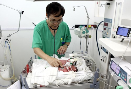 Doctor Nguyen Ngoc Loi at Hanoi's Central Ob-Gyn Hospital examines two of the quadruplets delivered at the hospital on November 27, 2014. They were conceived by IVF since their mother suffers polycystic ovary syndrome. Photo: Ngoc Thang