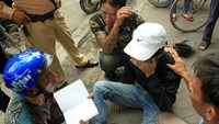 Ha Quang Hiep squats behind a drug addict that he rescued from an overdose in Hai Phong on November 5, 2014. A police officer was watching as Hiep's rescue team members gathered information from the addict. Photo: Vu Ngoc Khanh