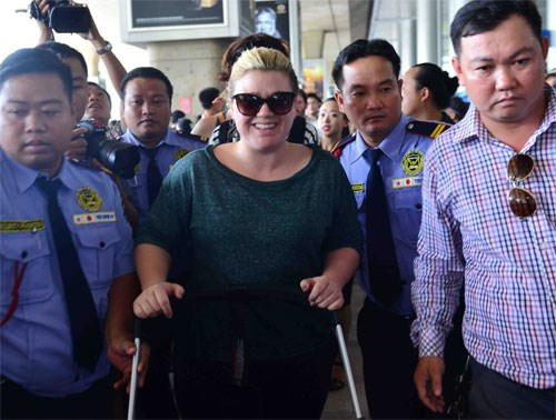 Security staffs escort Kelly Clarkson as she arrived at Tan Son Nhat Airport on December 1, 2014. Photo: Quoc Hung