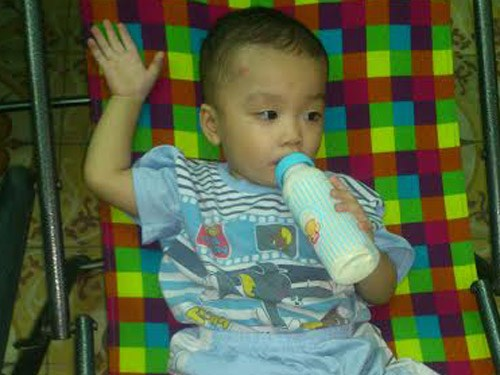 A photo provided by officials from Ward 1, District 8, Ho Chi Minh City shows a boy having milk at the ward office after a woman leaves him to a taxi driver early on December 2, 2014