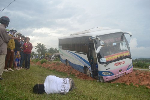 A drunk bus driver passed out in a ditch after insulting all of his clients and hitting several electric poles in Quang Ngai Province on May 4, 2014. Photo: Hien Cu