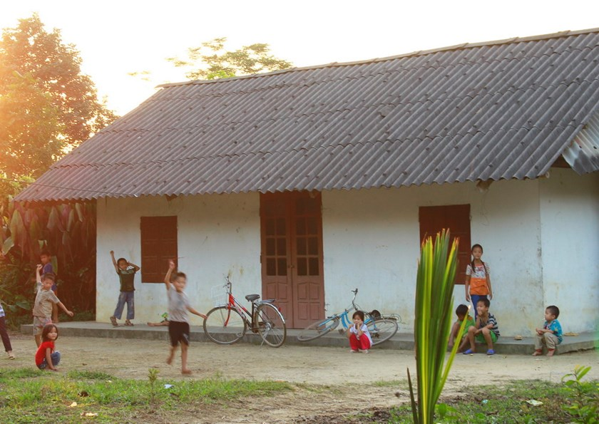 Children play in front of a house topped with white asbestos roofing tiles in rural Vietnam. Photo: Dan Ha
